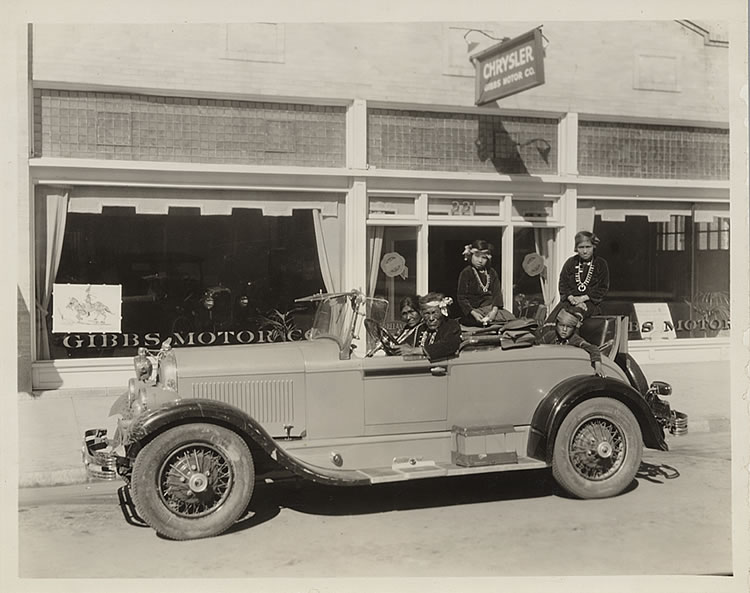 A group of Indians from La Osa Ranch posing in an automobile in front of the Gibbs Motor Company showroom, photographer unknown