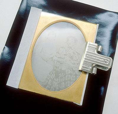 Daguerreotype plate being resealed, held by clamp while filmoplast is applied