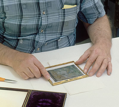 Brass preserver being replaced over newly sealed daguerreotype image package