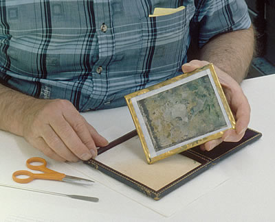 Brass preserver in place over newly sealed daguerreotype image package