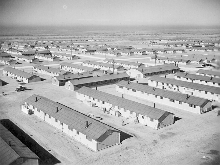 On a quiet Sunday afternoon at the Amache Center, the day is calm and the warm December sun invites center residents from their barracks homes. Photographer: Parker, Tom--Amache, Colorado. 12/13/42