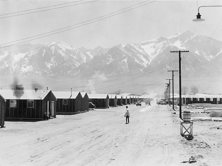 Manzanar, California--Street scene and view of quarters for evacuees of Japanese ancestry at Manzanar reception center. High Sierras in background. Photographer: Albers, Clem--Manzanar, California. 4/2/42