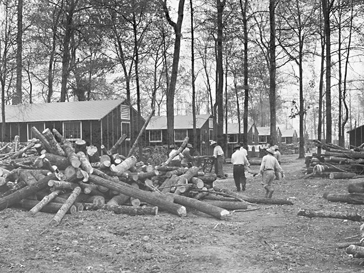 A typical wood cutting scene in the street in the north of the Rohwer Relocation Center, where former west coast residents of Japanese ancestry are now residing. Wood, to be cleared from the prospective center farm lands. The cutting is accomplished by volunteer teams selected by Block Managers, and each capable block resident contributes an equal amount of his time in sawing and chopping the logs. Photographer: Parker, Tom--McGehee, Arkansas. 11/21/42